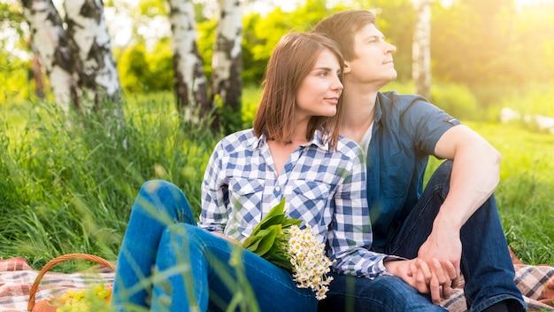 空き地にピクニックで休憩を持つ恋人