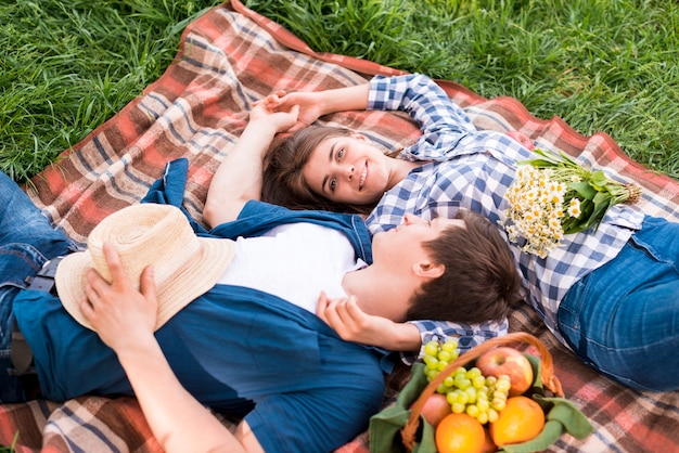 Молодая пара в любви, лежа на одеяле