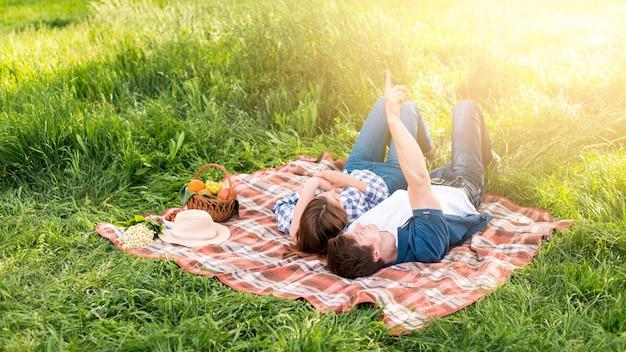 若いカップルが森の中で毛布で休む
