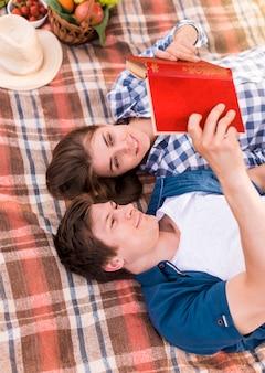 Молодая пара лежит на одеяле и читает книгу