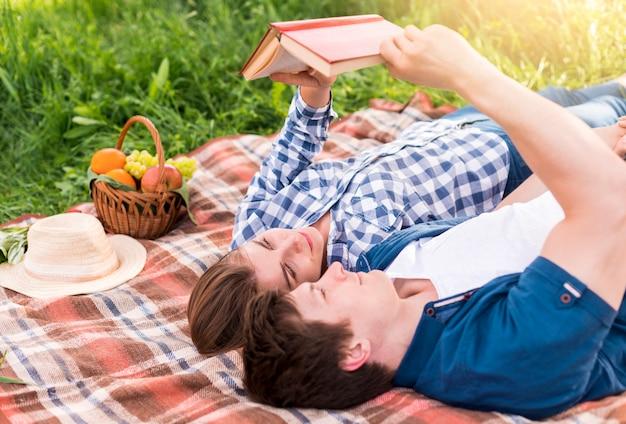 毛布で本を読んで楽しんでいる若いカップル