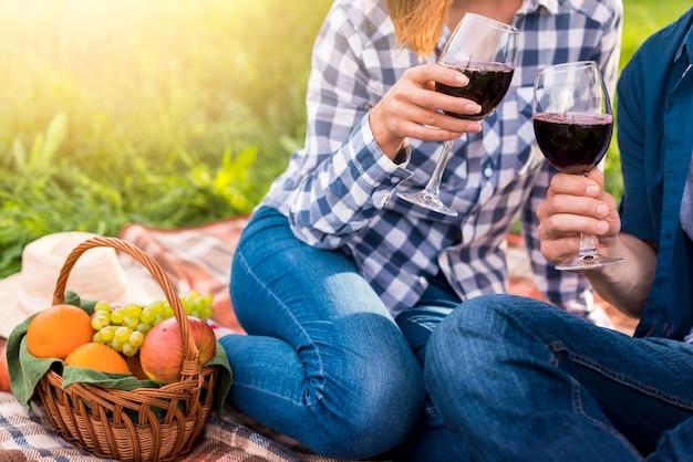 カジュアルなカップルのピクニックに赤ワインを飲む