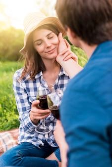 ピクニックに優しくガールフレンドの顔に触れる男