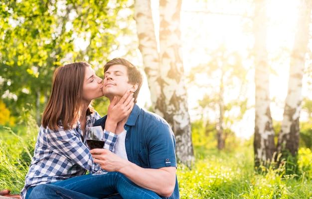 Женщина целует мужчину в щеку среди берез
