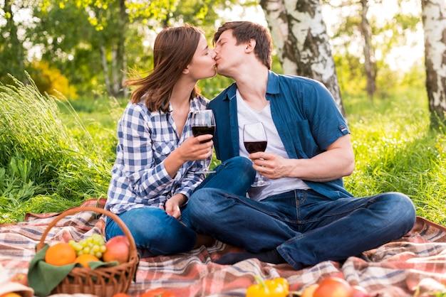 Молодая пара целуется на пикнике