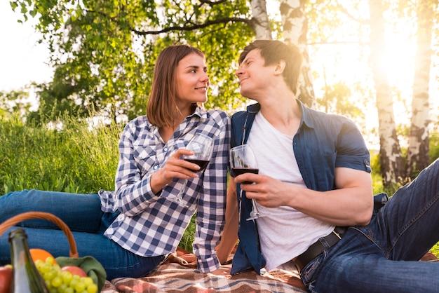 Парень и девушка пьют вино на пикнике