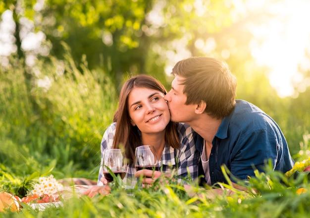 Мужчина целует женщину в щеку на пикнике