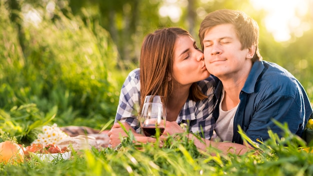 Женщина целует мужчину в щеку в лесу