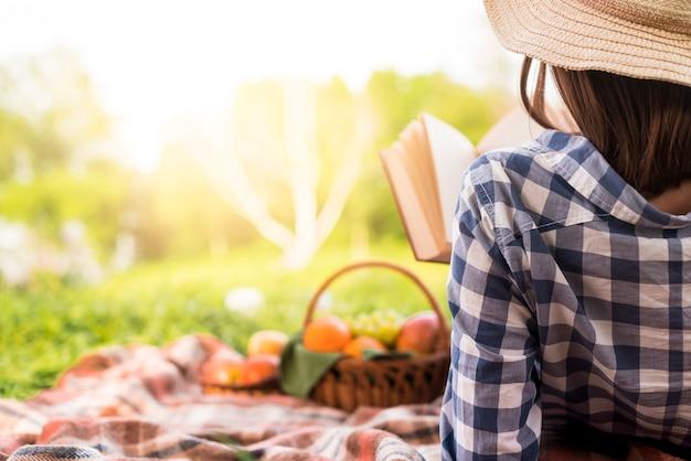 女性の公園でリラックスした読書本