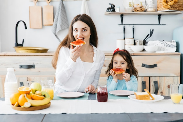 女性と女の子が台所で朝食をとって