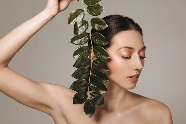 エキゾチックな葉でポーズブルネットの少女