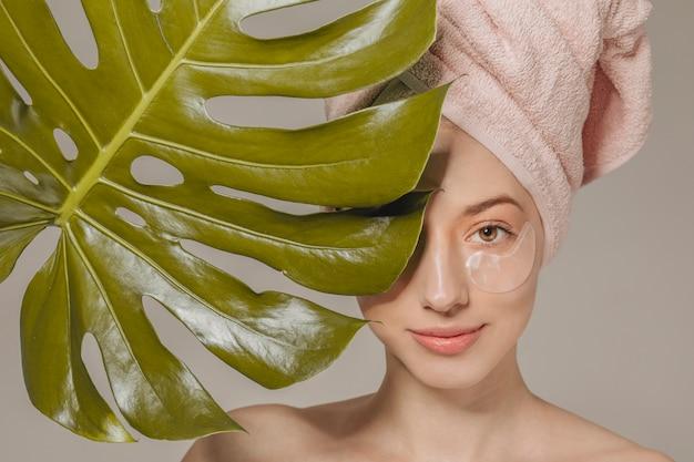 葉と頭の上のタオルを持つ少女