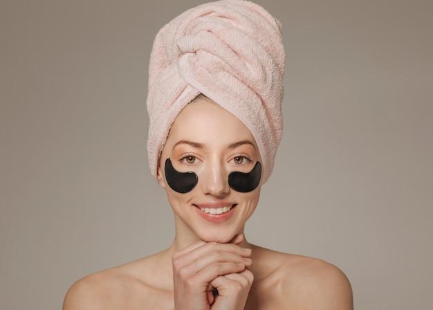 フェイスマスクと頭の上のタオルを持つ少女