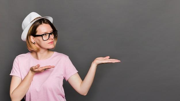 灰色の背景に対して何かを提示する帽子をかぶっている若い女性