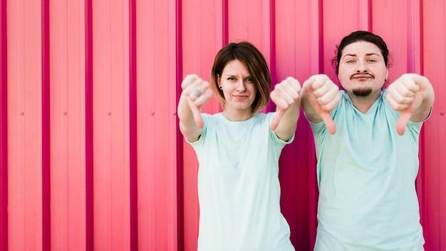 段ボール鉄の金属板に対して彼らの親指ダウンを示す若いカップル