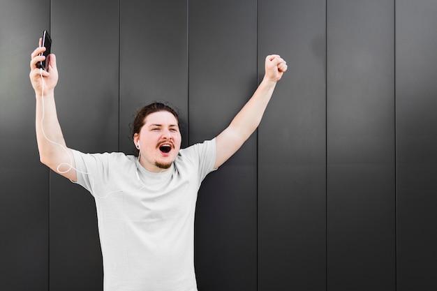 Возбужденный молодой человек поднимает руки прослушивания музыки на наушники против черной стены