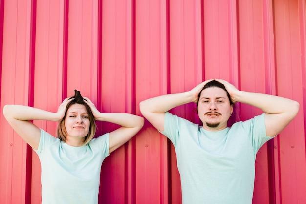 カメラ目線の頭の上の手で心配している若いカップル