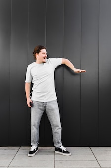 Музыка молодого человека слушая на наушнике через танцы мобильного телефона