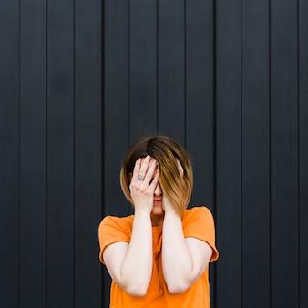 手で彼女の顔を覆っている黒い壁に立っている若い女性のクローズアップ