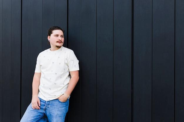 Портрет молодого человека с рукой в кармане, стоя у черной стены