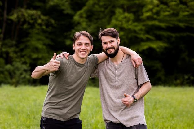 Веселые молодые люди, показывающие знак превосходства на поляне