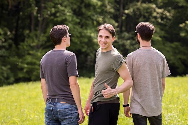 牧草地に戻って立っている友人と優秀なサインを作る若い男性
