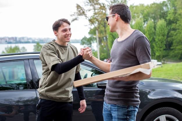 若い男性が車の近くの自然の中で挨拶