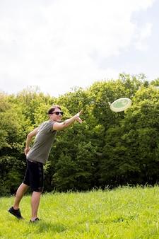 草原のフリスビーのプレートを投げて笑顔若い男性