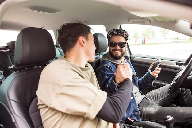 Друзья пожимают друг другу руки в машине