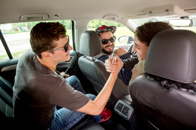 Компания молодых парней приветствует друг друга в машине