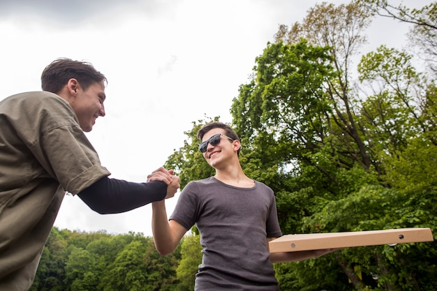 Молодые парни пожимают друг другу руки на природе