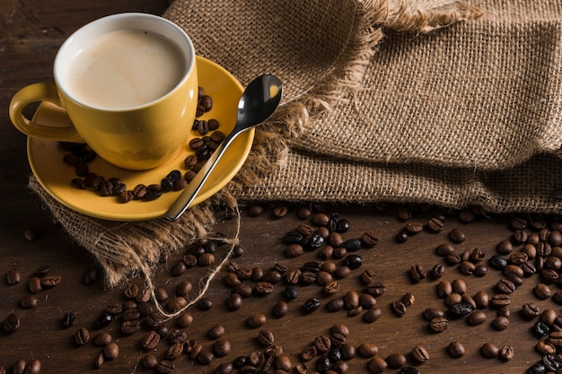 コーヒー豆の近くの荒布を着たコーヒー