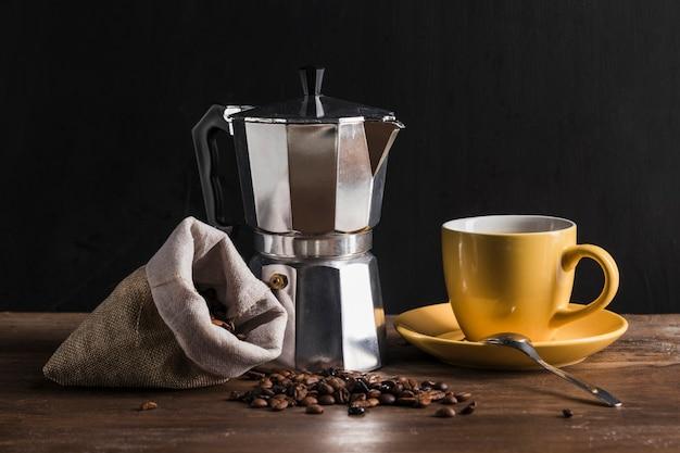 Кофеварка возле желтой чашки и мешок с фасолью