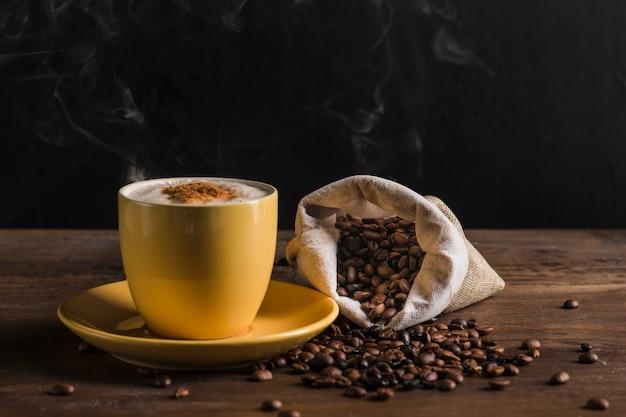 黄色の一杯のコーヒーと豆と袋