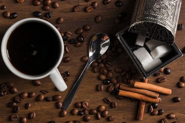 Чашка кофе с ложкой возле коробки с сахаром и палочки корицы