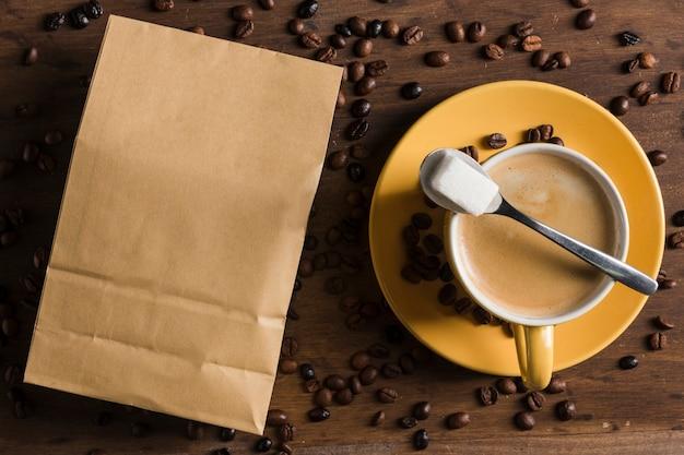 Чашка кофе и сахар возле упаковки
