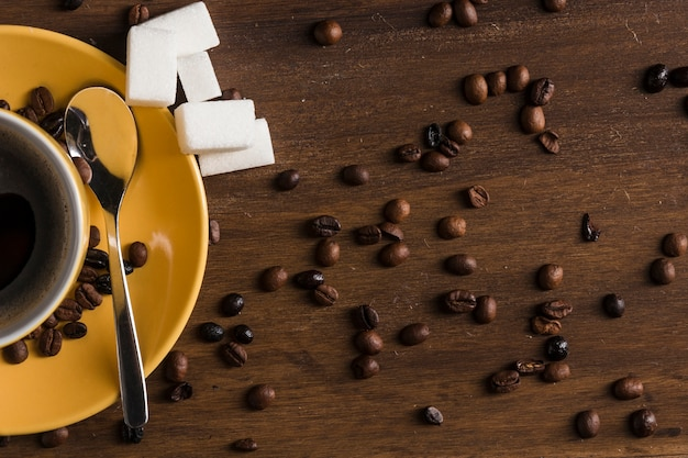 Чашка кофе и сахар возле бобов