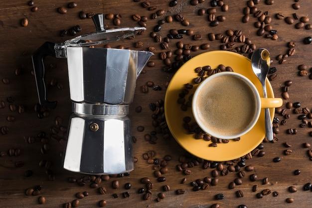 スプーンとプレートと黄色のカップの近くの間欠泉のコーヒーメーカー