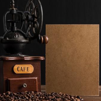 Картон и винтажная кофемолка возле бобов