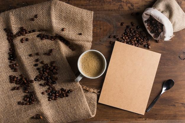 コーヒー豆と荒布と袋の近くの段ボールとカップ