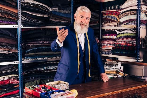 Портрет старшего мужчины модельера, приглашая кого-то в своем магазине