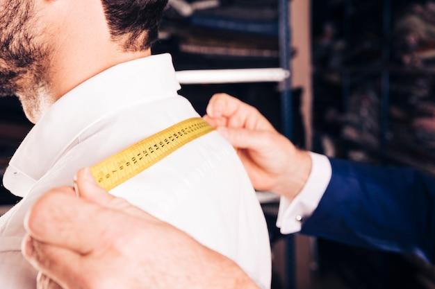 Модный дизайнер измеряет спину своего клиента желтой измерительной лентой
