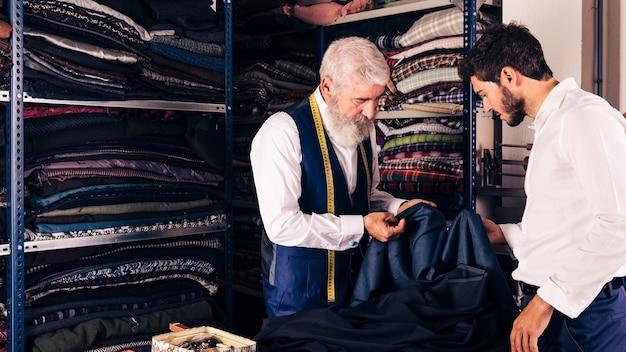 ファッション・デザイナーの店で彼の顧客に生地を見せる