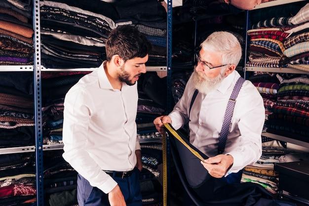 年配の男性が店で顧客に布の測定を行います