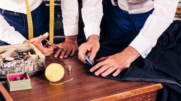 ワークショップでチョークでシニア男性仕立て屋マーキング布パターン