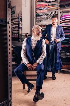 Мужской модный дизайнер держит пальто со своим клиентом, сидя на стуле в магазине