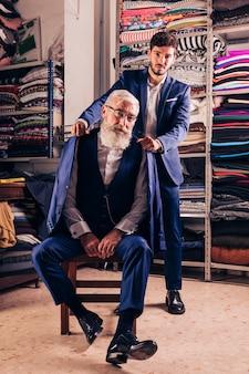 年配の男性の肩の上にコートをかざす男の肖像