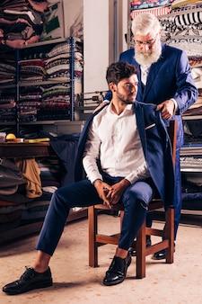 Мужской портной пробует синее пальто на своем клиенте, сидя над деревянным стулом в магазине
