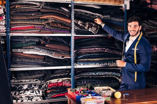 Улыбающийся портрет молодого мужского клиента, выбирающего ткань на полке