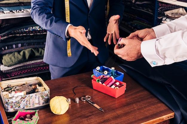 店で男性の仕立て屋に糸のスプールを示す顧客の手のクローズアップ